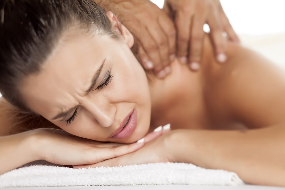 A woman on a massage table feeling some pain during a deep tissue massage.