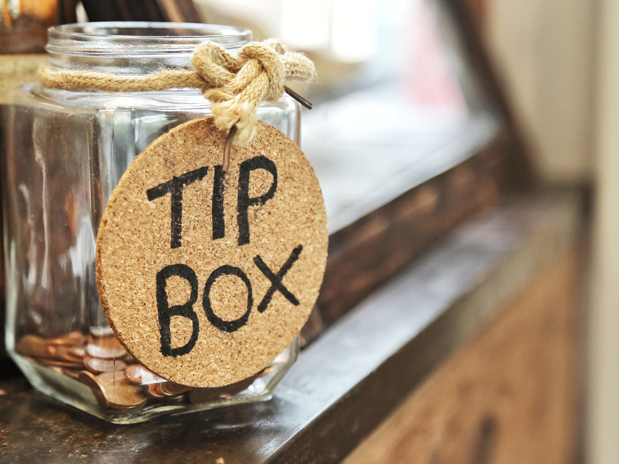 Glass jar with hemp rope tie tip box tag and few coins inside on wood counter